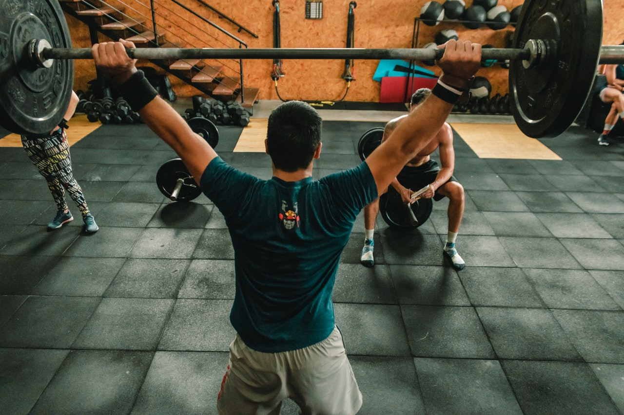 person-lifting-barbell-indoors-2261485